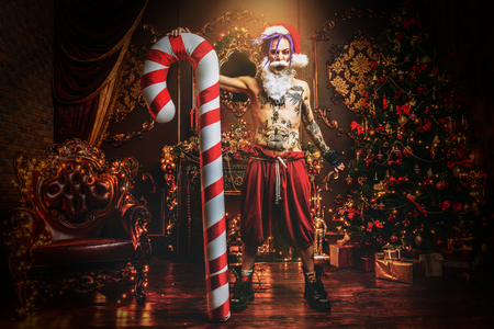 Bad Santa concept. Nude tattooed Santa with purple dreads holding a great Christmas Lollipop and is demonstrating antisocial behavior, rudeness and aggression in luxury apartments..