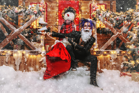 Cheerful punk Santa fools  and  ties the bag with gifts around near his house decorated with lights. Stock Photo