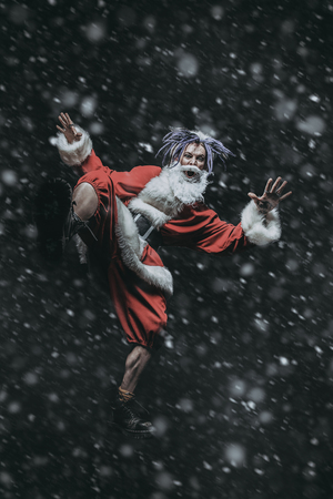 Full length portrait of a cool punk Santa Claus with bright dreadlocks over black background.