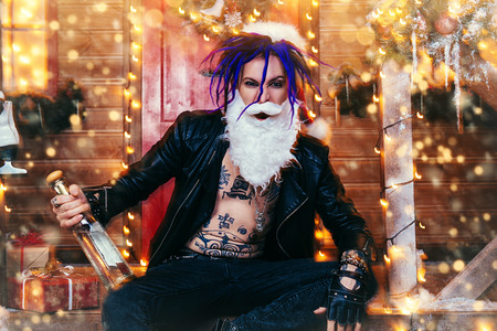 Drunk punk Santa is sitting with a bottle alcohol on the porch of the house, decorated for Christmas. Stock Photo