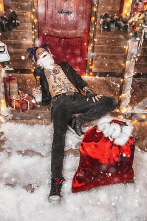 Drunk punk Santa is lying with a bottle and a bag of gifts on the porch of the house, decorated for Christmas.