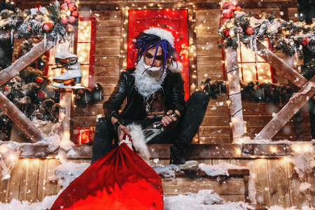 Drunk punk Santa is sitting with a bottle and a bag of gifts on the porch of the house, decorated for Christmas. Stock Photo