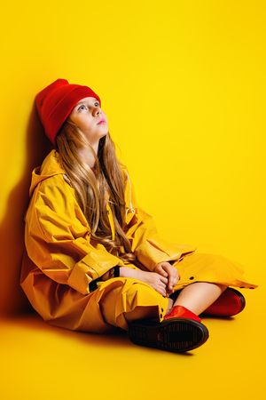 A bright fashionable girl in a raincoat and a hat. Autumn fashion for kids.
