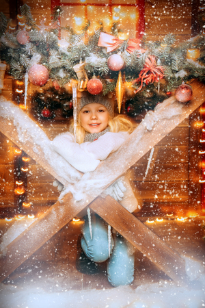 A pretty girl is on the porch in front of the house decorated for Christmas. Winter fashion for kids. Merry Christmas and Happy New Year.