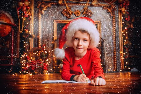 A portrait of a young boy writing a letter with wishes to Santa Claus. Decorations for Christmas and New Year. Time for miracles. Banco de Imagens