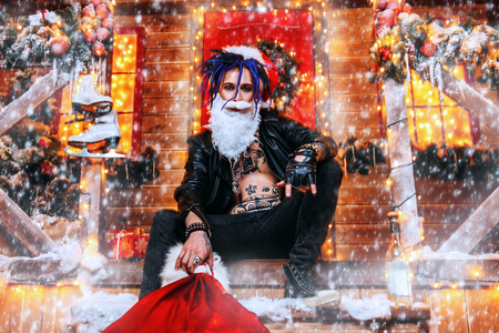 Cool punk Santa fools around near his house with a bag of gifts in his hands.