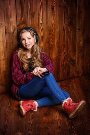Cute teen girl is listening to music with headphones in casual clothes on the floor.
