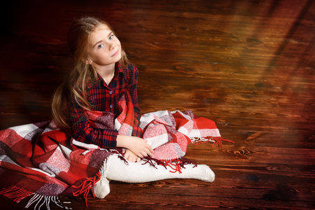 Сute girl is sitting covered with a plaid on a floor. Children's fashion.