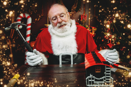 Santa Claus is sitting at a table at home. Merry Christmas and Happy New Year. Miracle time. Stockfoto