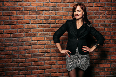 A portrait of a beautiful woman wearing classic clothes and posing over the brick wall in the studio. Beauty, fashion.