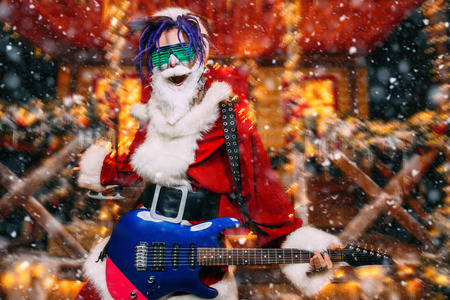 Perky punk Santa in luminous glasses stands with a guitar on the porch of the house, decorated for Christmas.