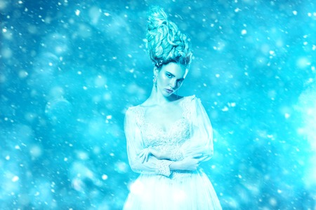 A portrait of a cold beautiful lady wearing a fluffy dress and posing in the studio over the blue background. Beauty,cosmetics, hairstyle, fashion.
