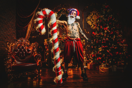 Bad Santa concept. Nude tattooed Santa with purple dreads holding a great Christmas Lollipop  and is demonstrating antisocial behavior, rudeness and aggression in luxury apartments decorated for Christmas. Stock Photo