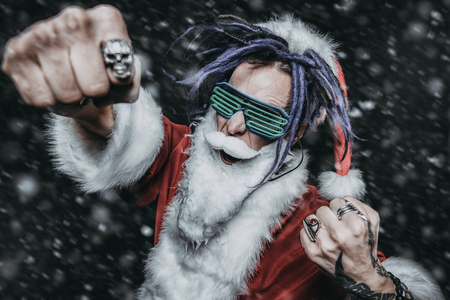 Cool punk Santa shows off clenched fists on a black background.