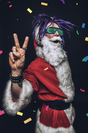 Portrait of a cool punk Santa Claus with bright dreadlocks over black background. Imagens