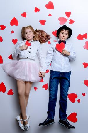 Heureux garçon et fille pré-adolescents posent entourés de cœurs. Amitié. Premier amour. La Saint-Valentin.