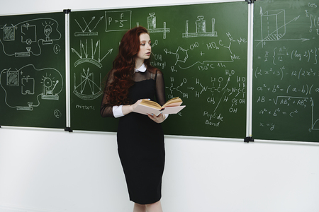 Pretty student girl with long red hair posing in school clothes by the chalkboard.