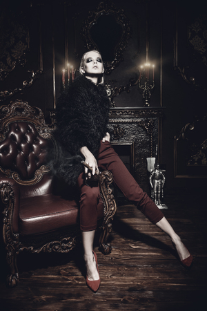 Seductive girl is posing on a leather armchair and smokes a cigar in a luxurious vintage interior. Fashion shot. Stock Photo