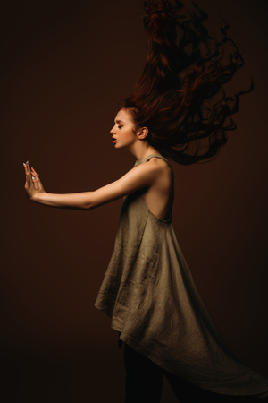 Modern  fifteen-year-old girl with long curly red hair is dancing in the studio. Beauty, fashion. Vogue dance.