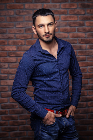 Portrait of a handsome brunet man standing by a brick wall. Men's beauty, fashion. Men's barbershop, Hairstyle. Stock Photo