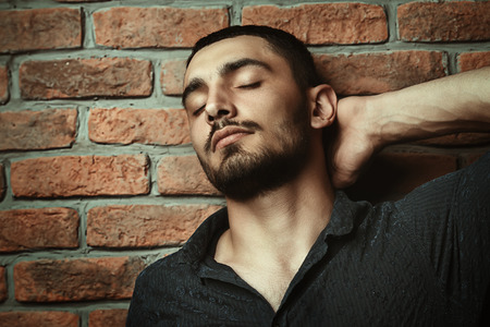 Close-up portrait of a handsome brunet man over brick wall background. Mens beauty, fashion. Mens barbershop, Hairstyle.