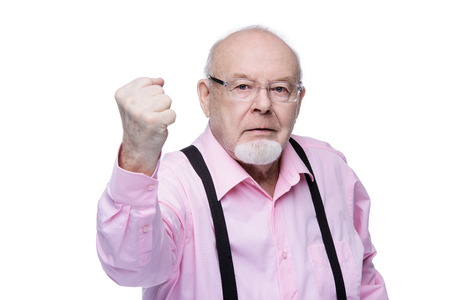 Old man in a fighting mood threatens with his fist. Social protection, rights of pensioners. Isolated over white. Copy space.