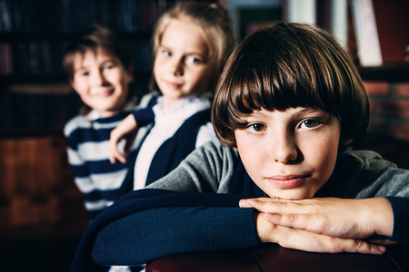 Three modern children posing in school uniform in luxurious apartments. School fashion.