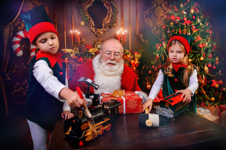 Santa Claus is giving presents to children at home. Merry Christmas and Happy New Year. Miracle time.