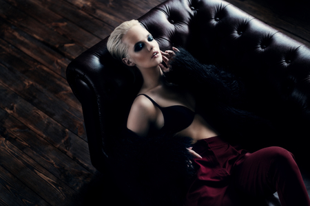 Seductive girl in the black bra, red pants and  fur jacket lying on a leather sofa. Luxurious lifestyle. Fashion, beauty. Studio shot.
