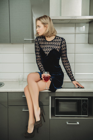 Fashion shot. Beautiful female model with short hair is posing in cocktail dress sitting on the countertop of the kitchen set. Beauty, fashion.