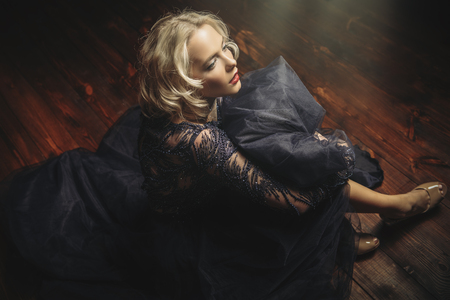 A cute blonde lady is sitting on the floor. Evening dress. Fashion, beauty. Reklamní fotografie