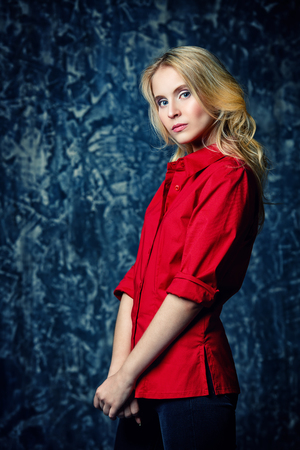 Portrait of a blonde girl in red elegant shirt over grunge background. Beauty, fashion concept. Studio shot.