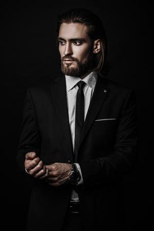 Modeschuss. Hübscher junger Mann, der im eleganten Anzug und im weißen Hemd über schwarzem Hintergrund aufwirft. Herrenschönheit, Mode.