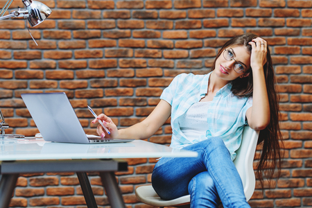 A beautiful lady is sitting at a table. Office life. Work place. Imagens - 115258756