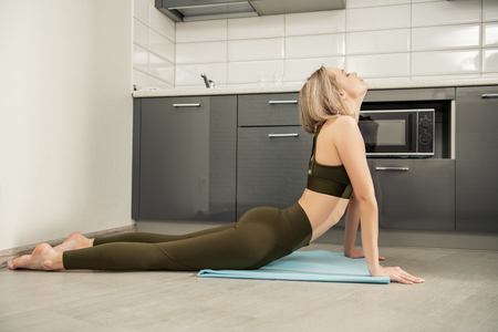 Portrait of a beautiful sexy girl is practicing yoga on the floor in the kitchen at home. Fitness at home, yoga. 写真素材