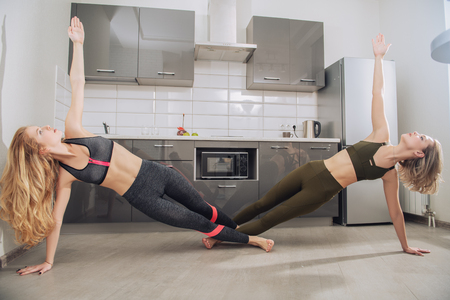 Two girlfriends are doing exercise for the body on the floor in the kitchen.