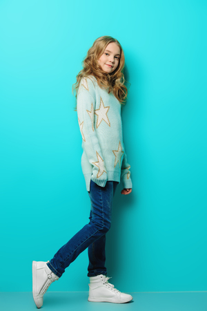 Pretty nine year old girl poses over blue background and smiling. Kid's fashion. Spring style. Stock fotó