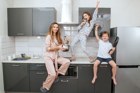 Young woman and her children are funing with the kitchen utensils in the kitchen. Family home shoot. Imagens