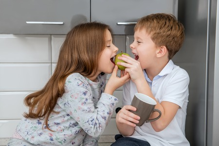 Cute girl and boy are eating an apple in the kitchen at home. Childhood. Kids fashion