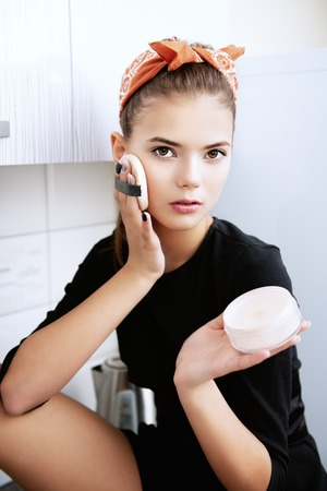 An attractive young girl is posing with sponge, cream and with a headband on the kitchen. Pin-up style. Stok Fotoğraf