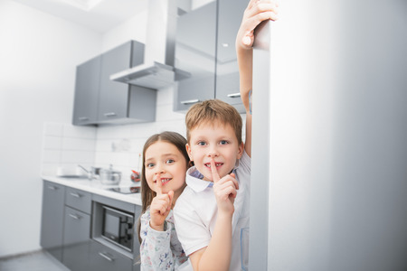 Two cute kids hiding behind the fridge in the kitchen. Childhood. Kid's fashion. 版權商用圖片