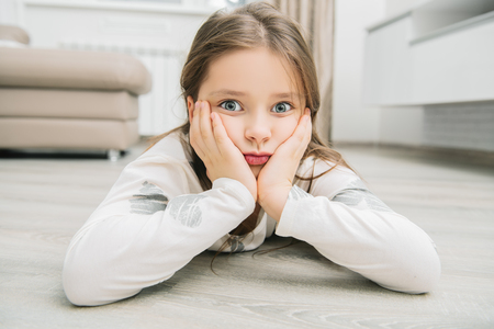 A pretty thoughtful little girl is lying on the floor in the room.  Childhood. Kids fashion.