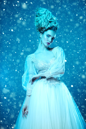 A portrait of a cold beautiful lady wearing a fluffy dress and posing on a snowy blue background. Beauty,cosmetics, hairstyle, fashion. Stock Photo - 115320983