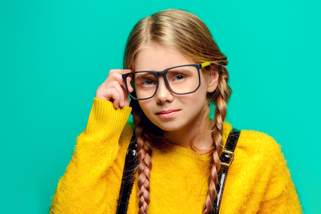 Cute nine year old girl posing in studio in fluffy yellow dress over turquoise background. Childrens beauty and fashion.