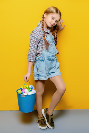 Children's fashion. Cute nine year old girl with long blonde hair is posing in summer clothes with a bucket of easter eggs. Studio shot. Full length portrait.