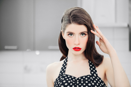 Portrait of attractive young woman in a black dress with white dots  is posing on kitchen background. Pin-up style.