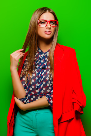 Fashion shot. Beautiful sexy woman is posing in bright clothes over green background. Beauty, fashion concept. Stock Photo