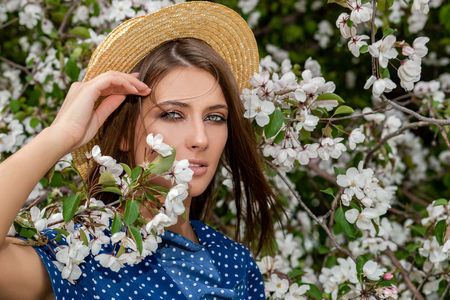Beautiful girl in a straw hat is posing in a blooming garden. Beauty, fashion. Stock Photo