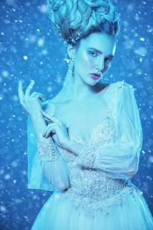 A portrait of a cold beautiful lady wearing a fluffy dress and posing on a snowy blue background. Beauty,cosmetics, hairstyle, fashion. Stock Photo - 115319908