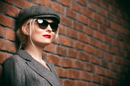 Portrait of a sexual young woman wearing gray jacket, cap and glasses. Beautiful smart girl. Beauty, fashion.